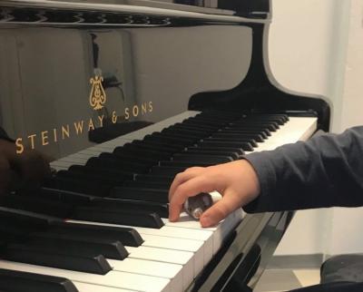 Käsi pianon koskettimilla pitää leikki hiirtä kämmenensä alla.